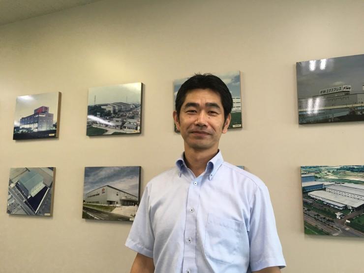 (人財部で社内全体を見渡す市川さん、背景は海外拠点の写真)